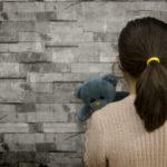 little girl facing a wall, holding her stuffed bear
